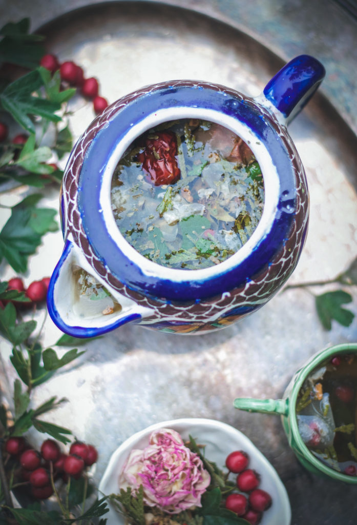 close up of an herbal tea blend in a blue and brown tea pot