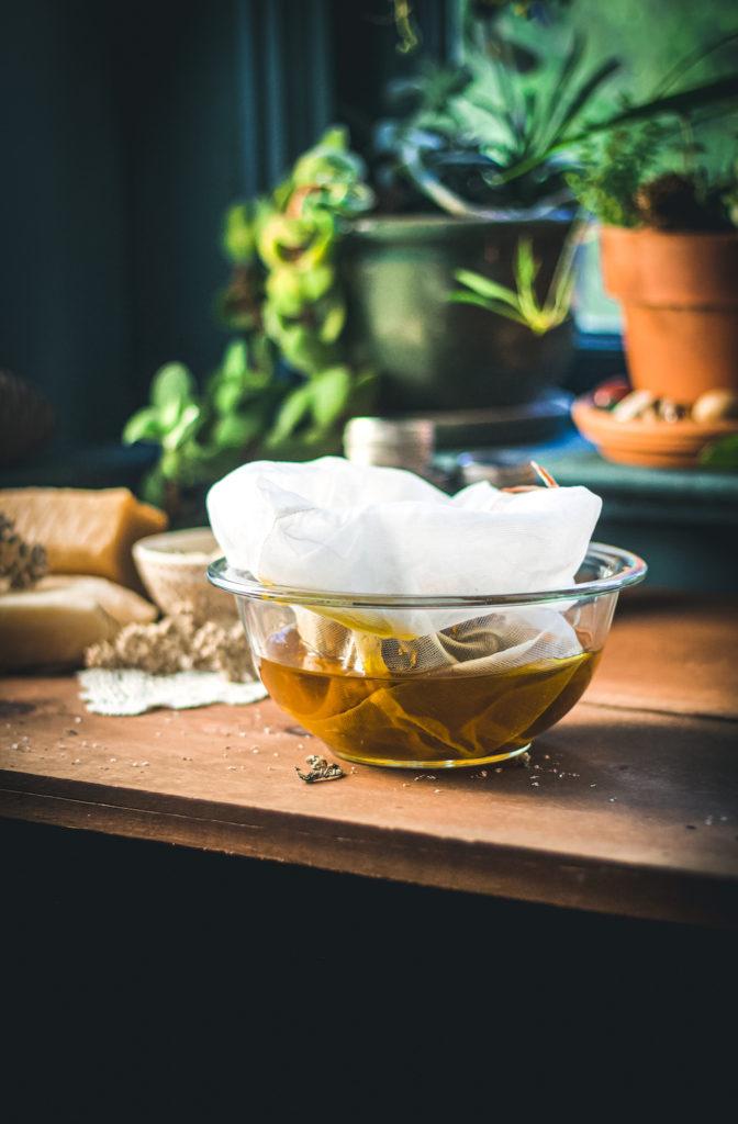 herbal oil straining through a jelly bag