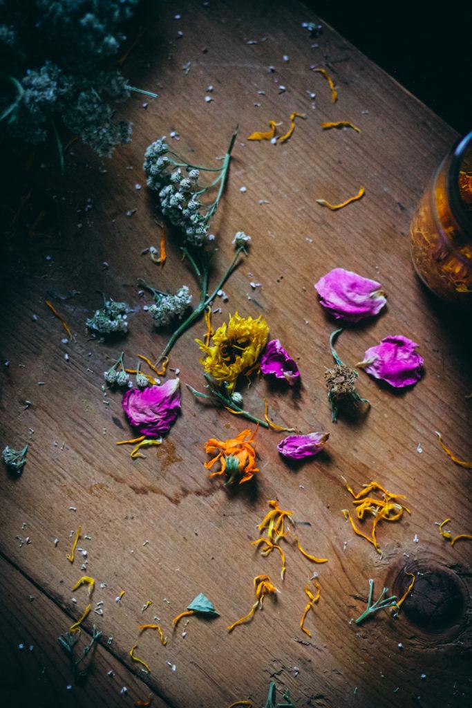scraps of calendula rose yarrow on a wood surface