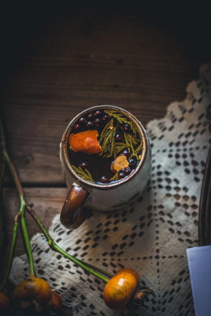 orange peel, cedar, rose hips, cinnamon, juniper berry herbal tea in tea mug