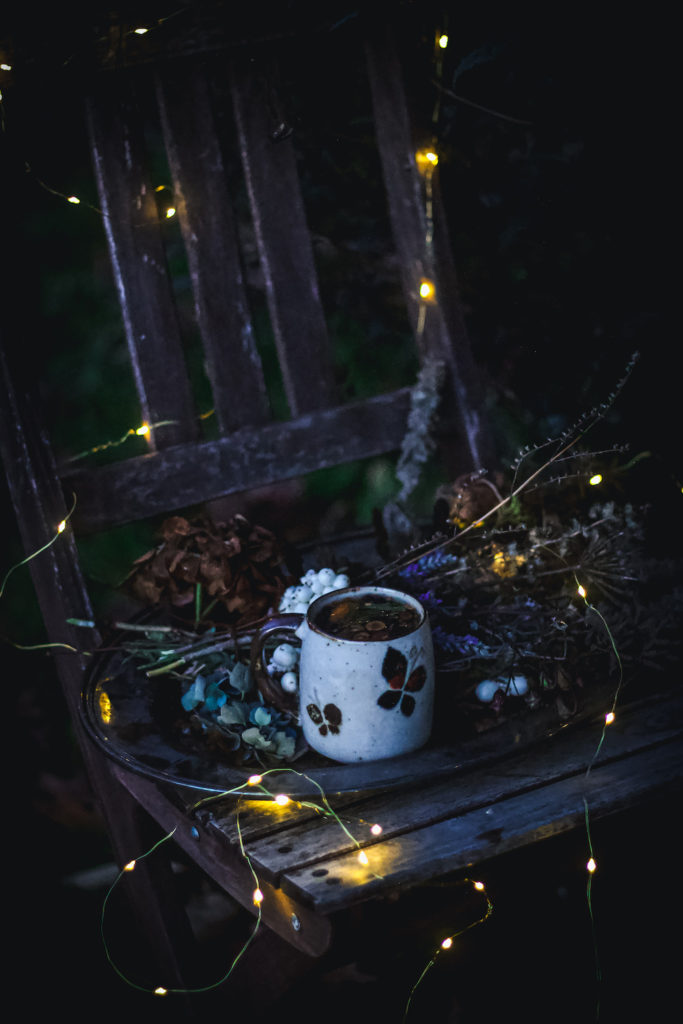 dried flowers and tea on tray on chair in dark outside with twinkle lights