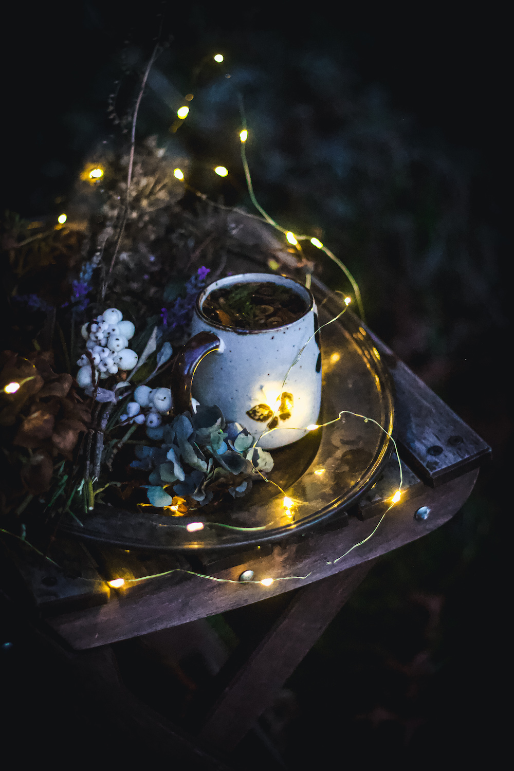 herbal tea in mug outside in dark with dried flowers and lights