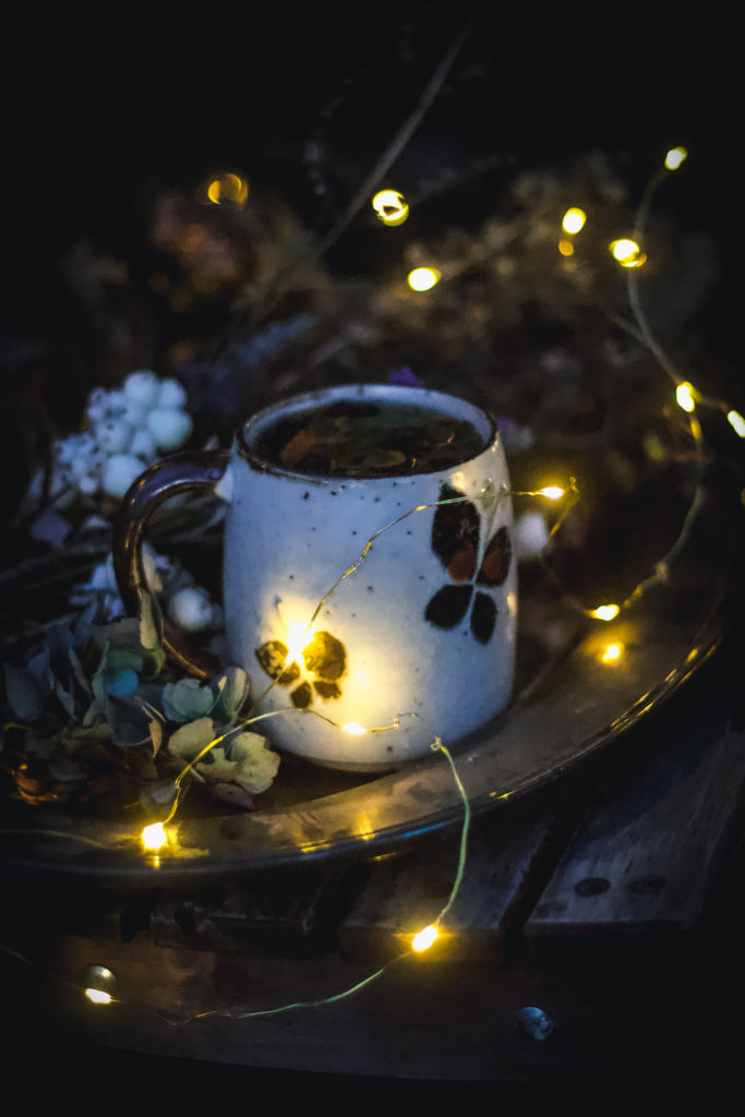 tea mug on tray in dark outside with twinkle lights
