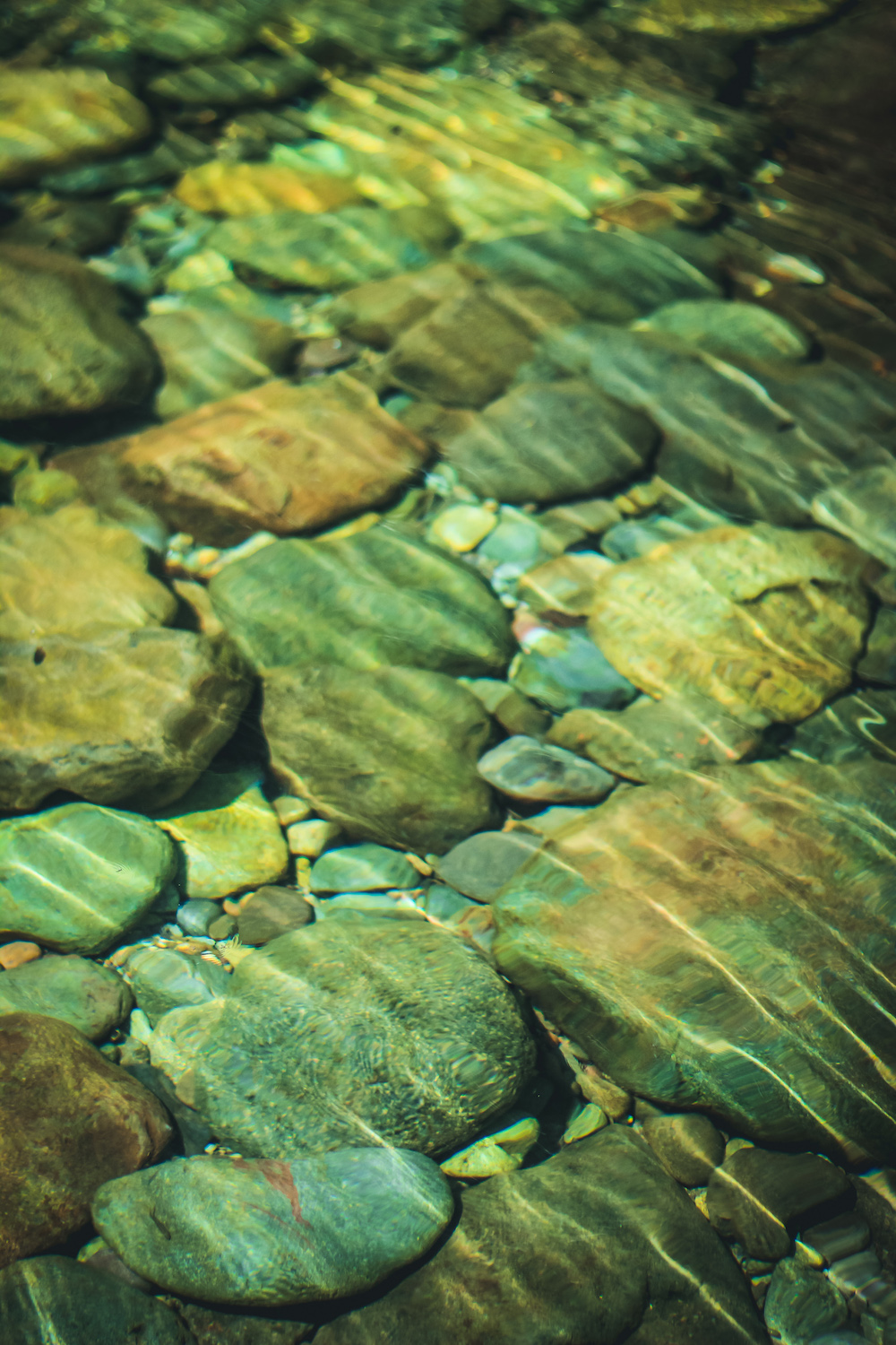 turquoise and tan river rocks under water