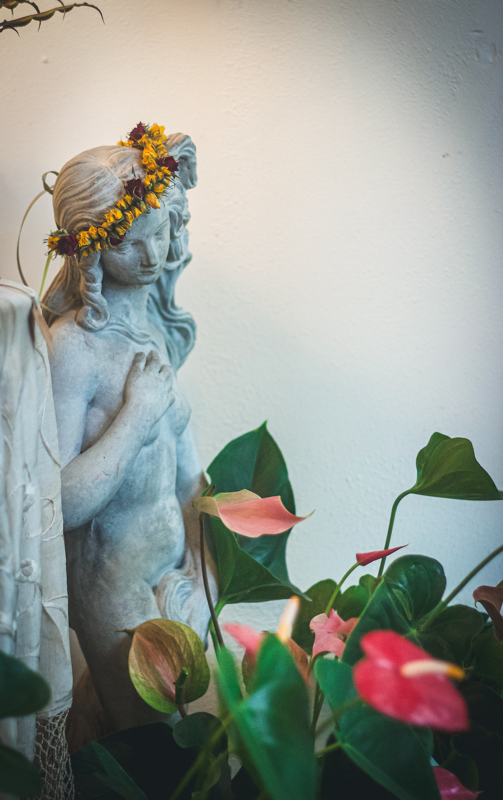 statue of women in front of pink peace lilies