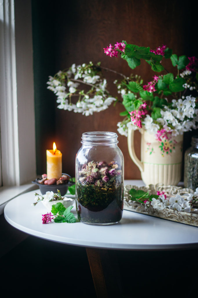 nettle herbal tea blend on table with flowers and candle