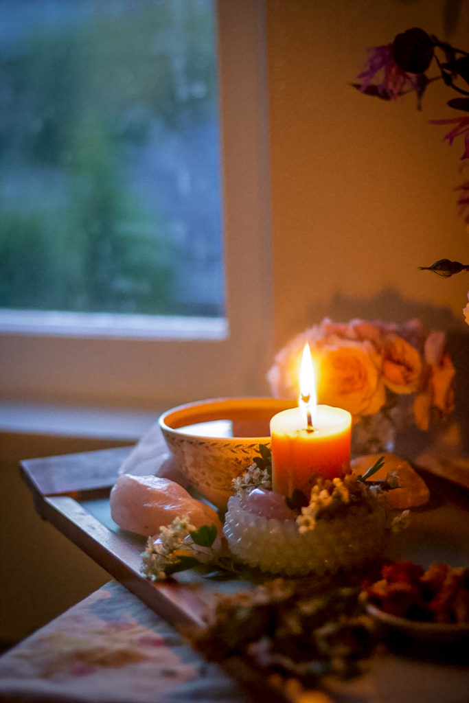 candle and tea cup with window in background