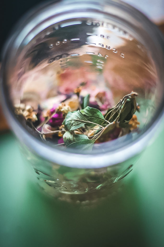 hawthorn flower and rose tea in glass jar close up