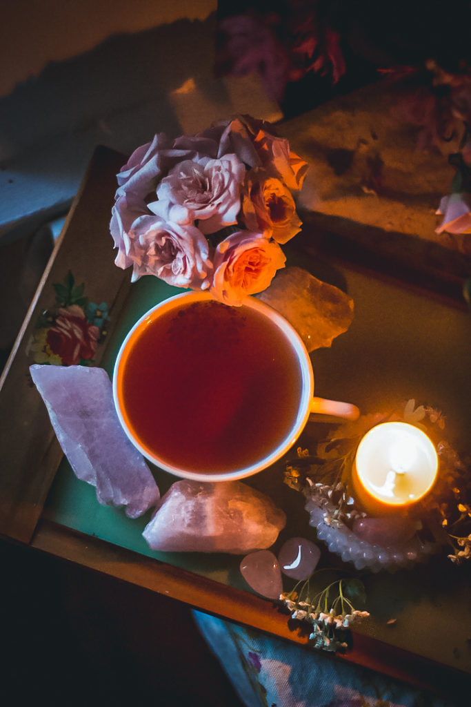 pink tea in round tea cup on green tray with candle and pink quartz