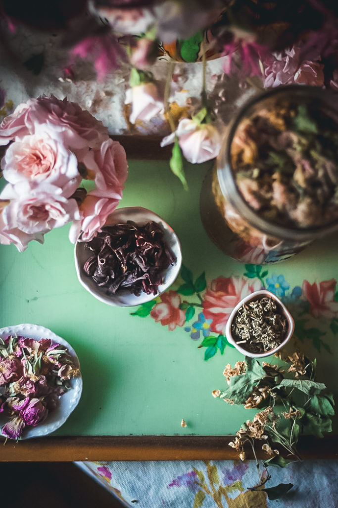 herbal tea ingredients on green tray with pink roses
