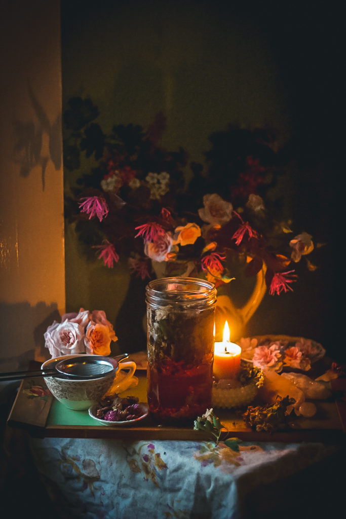 herbal tea steeping in jar with flowers and candle