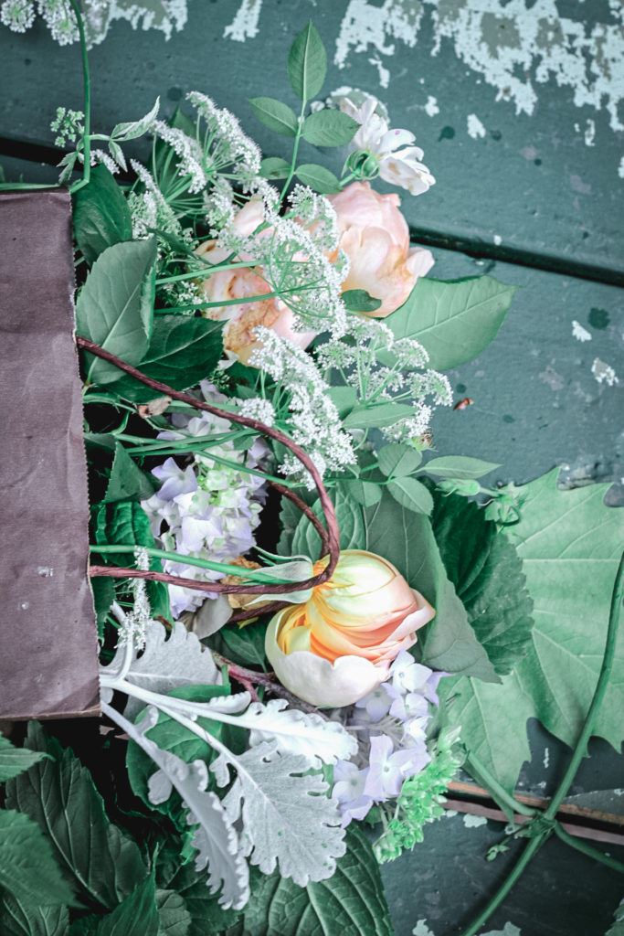bag of flowers on green bench